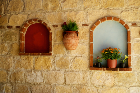 Decorated stone wall with flowers and windows