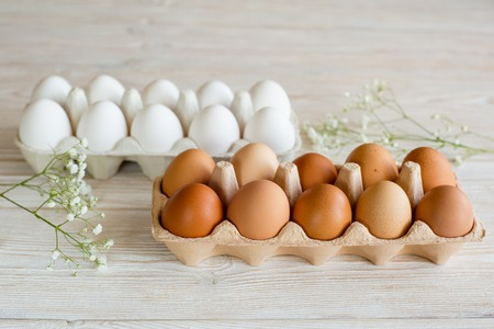 white eggs: brown and white eggs on a white wooden table