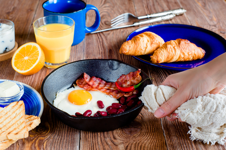 english breakfast: serving of an english breakfast in rustic style. fried eggs with beans and bacon on a frying pan. toasts and croissants on a blue plates. first person view Stock Photo