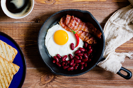 english breakfast: english breakfast in rustic style. fried eggs with beans and bacon on a frying pan. toasts on a blue plates. close up, top view Stock Photo