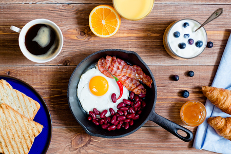 english breakfast: english breakfast in rustic style. fried eggs with beans and bacon on a frying pan. croissants and toasts on a blue plate. Cup of coffee, yogurt and orrange juice. top view Stock Photo