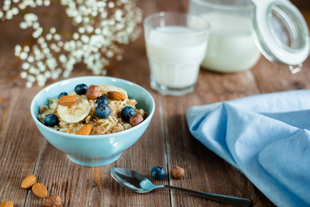 breakfast bowl: Breakfast with oatmeal porridge with berries and nuts. milk porridge in blue bowl on brown wood table. horizontal, colorfull