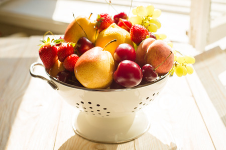mixed fruits: Fresh mixed fruits, berries in bowl. Love fruit, berry. Fruits, berries in bowl in sunlight near the window. Healthy eating, dieting. Summer food, clean eating. Stock Photo