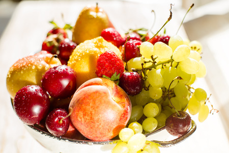 mixed fruits: Fresh mixed fruits, berries in bowl. Wet fruits, berries with water droplet in bowl in sunlight near the window. Healthy eating, dieting. Summer food, clean eating.