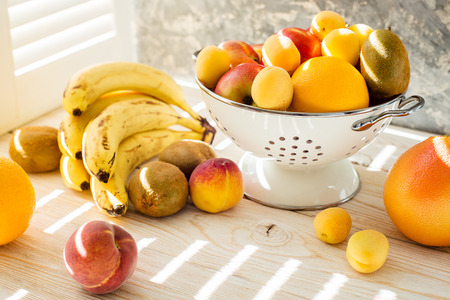 mixed fruits: Fresh mixed fruits in bowl on white background. Fruits in sunlight near the window. Healthy eating, dieting. Summer food, clean eating.