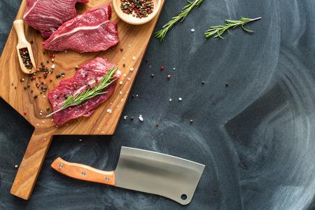 frisches Fleisch auf Schneidebrett mit Rosmarin, Salz, Pfeffer und Messer. Rohes Fleisch. drei Peece von Rindfleisch bereit zum Kochen auf Holzbrett auf schwarzem Hintergrund. Nahansicht. Draufsicht. Platz für Text