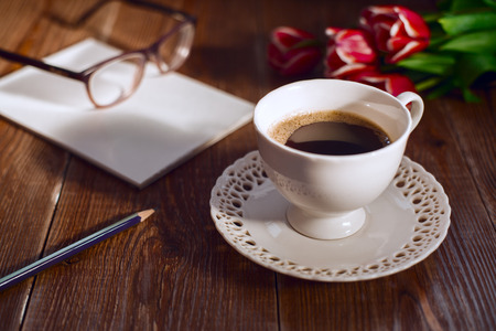 glases: Coffee cup with note book and glases and flowers. Retro style pictures