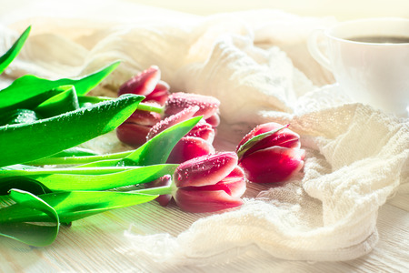 coffeetime: Red flowers tulips and cuf of coffee on light wood backgroung. Morning light. Stock Photo