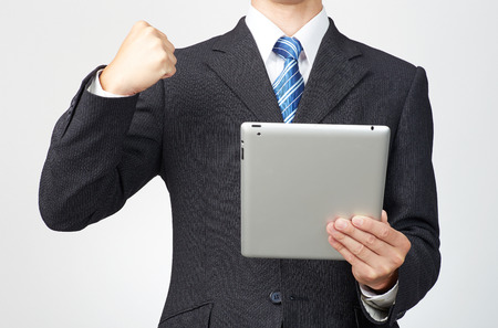 clench: businessman holds tablet, no face