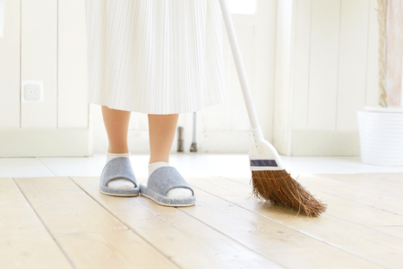 smiling Asian woman cleaning the room