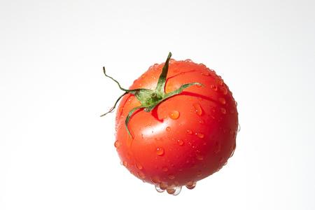 Ripe tomato with water splash isolated on a white background. Zdjęcie Seryjne