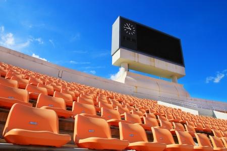 grandstand: row of orange seats and score board Stock Photo