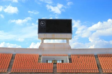 grandstand: fila de asientos de color naranja y tabla de puntuaci�n, cielo azul y nubes backgroud