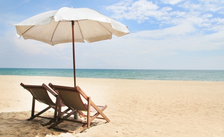 Two chairs under umbrella on beautiful tropical beach in thailand