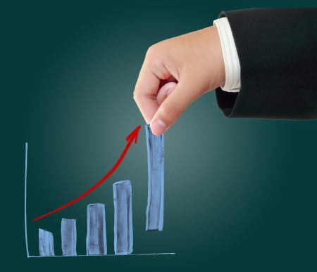 Hand of businessman pulling up a bar from business growth graph photo