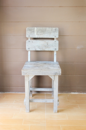Old wood chair in front of brown wall photo