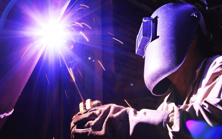 construction safety: Industrial worker make a spark welding, working place background.