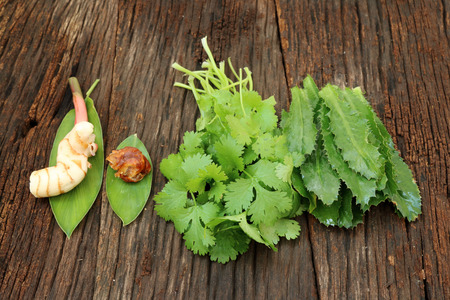 Galangal ginger,parsley and thai vegetable herb on wood background photo
