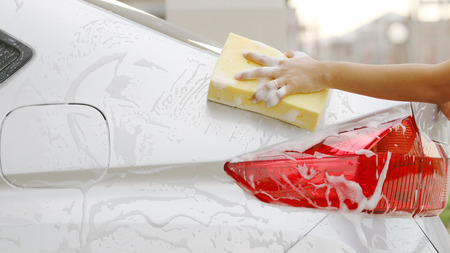 Woman Washing a silver car with a yellow sponge and soap bubble.