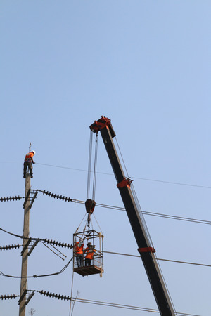 Electrician working at height by connect a high voltage wire, mobile crane lifting against the blue sky photo