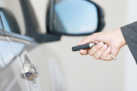 black and white lock: Business woman operate remote key car for open lock door.