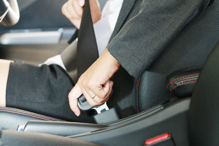 Business woman hand fastening a seat belt in the car. Zdjęcie Seryjne