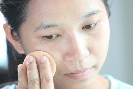woman applying make up by press face powder