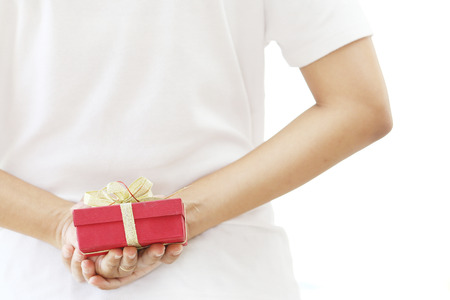 gift behind back: woman hiding red gift box behind her back, isolate on white background. Stock Photo