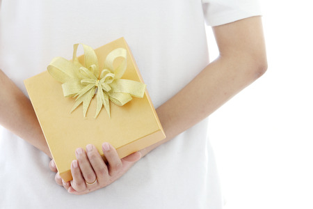 gift behind back: woman hiding gold gift box behind her back