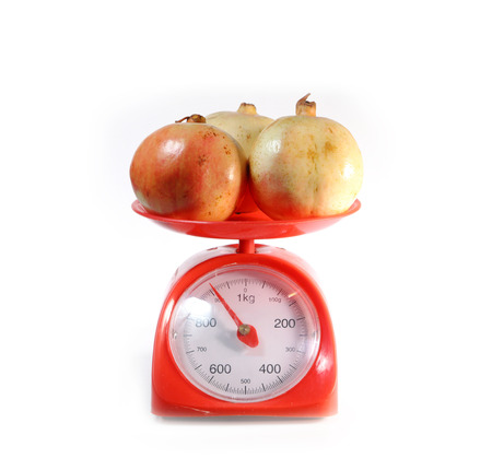 weighing scale: pomegranate on red weighing scale, isolate on white background Stock Photo