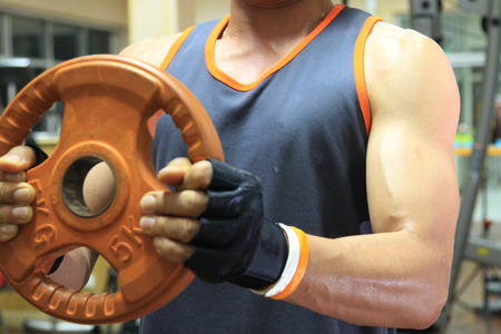 hand weights: Exercising in the gym, Strong man lifting hand weights. Stock Photo