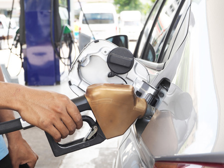 refilling: Male hand refilling fuel to car on a gas filling station Stock Photo