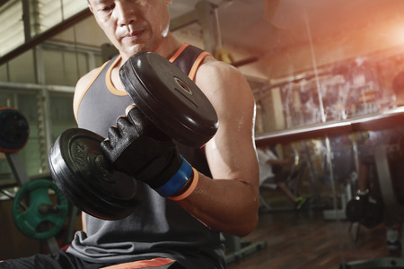 asian bodybuilder: Muscular man working out with dumbbells.