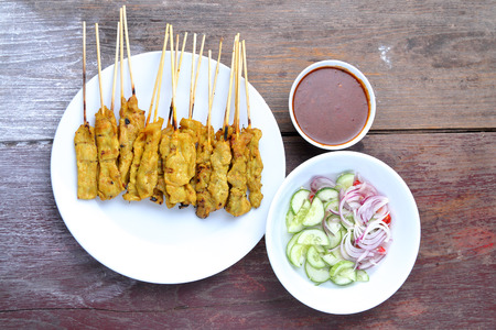 satay sauce: Pork Satay with Peanut Sauce, Wood table background.View from above.