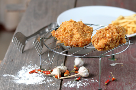sieve: Fried Chicken on sieve, powder on wooden floor background.