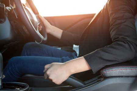 hand brake: Business woman driver pulling the hand brake in car, in car background. Stock Photo