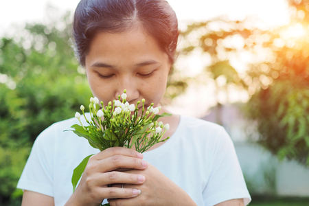 Asian woman smelling flowers in garden. Stock Photo
