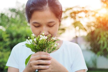 asian woman: Asian woman smelling flowers in garden. Stock Photo