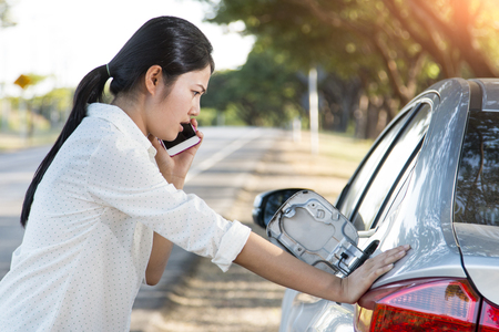 calling for help: Car oil down and Young woman trying to calling for help on phone. Stock Photo
