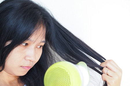 haircare: Haircare. Beautiful long haired woman blowing, drying hair, white background.