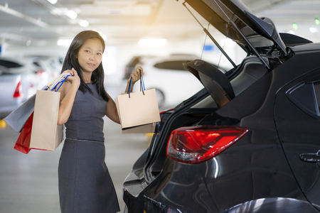 Asian women keep shopping bags at the back of the car. The parking lot is a shopping mall.