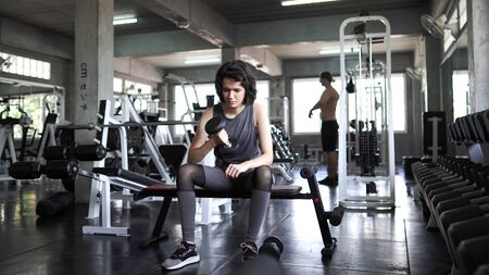 Sporty young women exercise by lifting dumbbells in the gym,  concept gym and bodybuilding.
