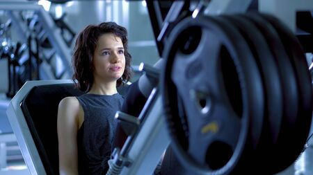 Young sporty woman training by press legs in gym, quads machine press at gym.fitness and bodybuilding concept.