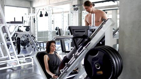 Male instructor, trainer is teaching young sporty woman how to do leg presses in the gym. Stock Photo