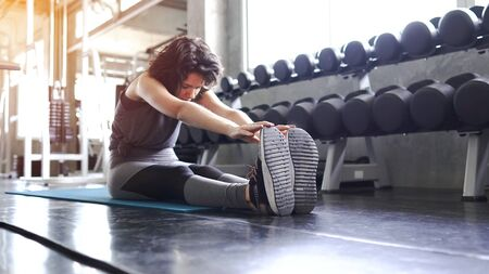 Woman in an athletic look with aerobic exercise stretching loosening the muscles in various positions while on the exercise mat. Stock Photo