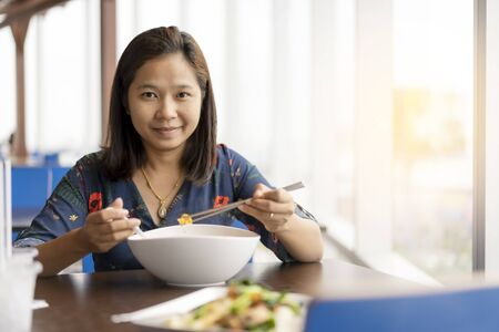 Asian woman sit near the window and happy enjoy with chineses noodle food.
