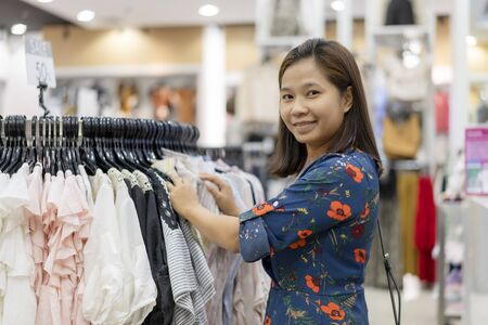 Asian woman choosing her fashion outfit clothes in closet at store.