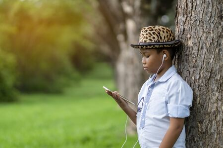 Asian boy is listening to music using headphones with a smartphone at the park.