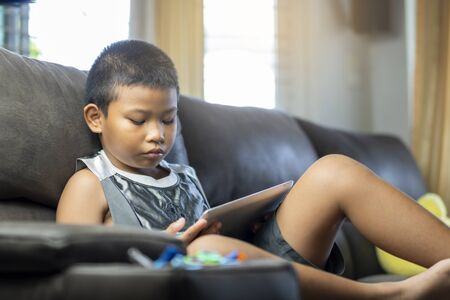 Asian boy playing game or watching cartoons on digital taplet or smartphone on sofa living room.