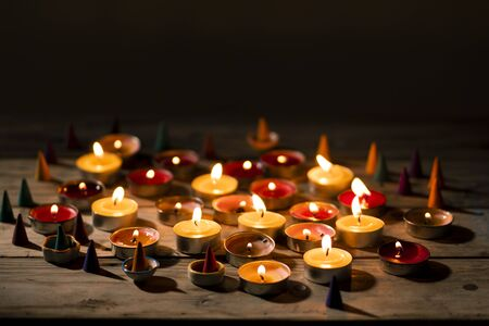 Lighting candle on wood table. Many candle flames in darkness.